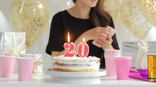 Beautiful young woman with birthday cake and balloons against defocused lights 1080p fullHD.