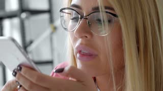 Brazilian business woman talking into mobile phone using artificial intelligence recording voice memo creative team working in background office close up 20s 4k