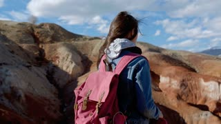 Brunette 20s female in a denim jacket and a pink backpack admiring the mountains in windy weather close-up 4k.