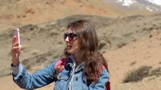 Brunette 20s girl in sunglasses, denim jacket and pink backpack makes a photo of a spring canyon with a river, sitting on the rock 4k.