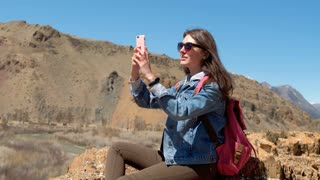 Brunette in sunglasses and pink backpack makes a photo of a spring canyon with a river 4k