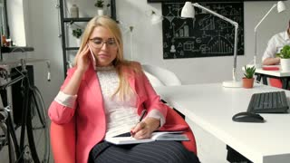 business concept - businesswoman talking on the phone in office close up 20s 4k