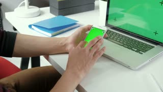 Business man using smart phone, checking information on cell phone with green screen on brown background with laptop. Hands top view. Office desk background. 20s 4k.