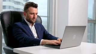 Businessman in formal wear using laptop in office