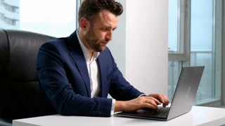 Businessman typing on the laptop in office