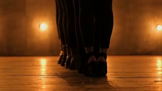 Close up Silhouettes of dancing girls. go-go dance. Closeup dance performance of pretty female group on a dark stage with yellow lights. team dance of women in high heels. 1080 slow motion