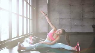 Dedicated to fitness. Front view of beautiful young woman in sportswear doing stretching while sitting on the floor in front of window at gym 20s 4k.