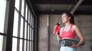 Fitness woman drinking water from bottle. Muscular young female at gym taking a break from workout. 20s 4k.