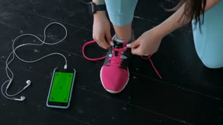 Flat lay of mobile phone with earphone and sport equipment on wood background. Woman in black sneaker with sport equipment, top view 20s 4k.