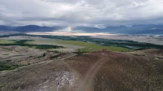 Friends hiking on vacation,relaxing on top of the mountain, looking at beautiful rainbow at sunset , mountains landscape. 4k slow motion aerial shot
