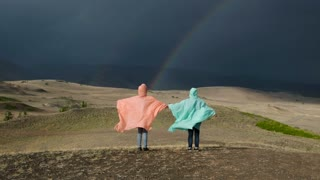 friends holding hands stand on a background of a mountain landscape with a rainbow. are dressed in raincoats. 20s 4k.