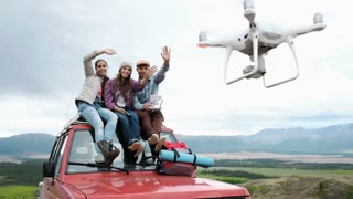 group of friends doing selfie on drone sitting on red car on mountain backdrop background. 20s 4k