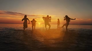 Group of happy girls running and playing in water at the beach on sunset. Beauty and joyful teenager friends having fun, dancing, spraying over summer sunset. Beach party. Sun flare. Slow motion.
