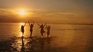Group of happy girls running and playing in water at the beach on sunset dancing, spraying over summer sunset. Beach party. Sun flare. Slow motion