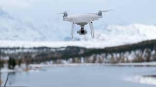 Hovering drone taking pictures of white winter nature.