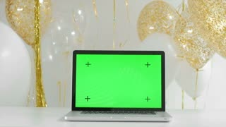 laptop with isolated green screen. Golden and silver balloons background. New Year concept. 1080p fullHD