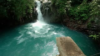 Man jumping in the river with waterfall slow mo