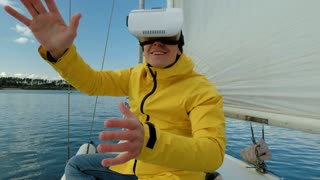Man with Virtual Reality glasses, enjoying sitting on sailing boat and looking happy.