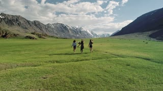 Three girlfriends running free on green grass meadow sunny day and background of mountain - Friendship girls and freedom concept with young happy women moving free at camping experience tossing hats