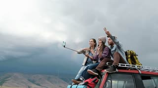 Three happy hipster young women taking selfie sitting in a vintage van during a summer road trip 20s 4k.