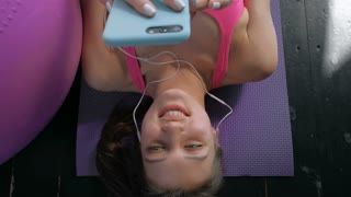 top view Active girl with smartphone listening to music in gym. 20s 4k