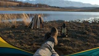 Tourist tent inside with men's feet, sunny 20s 4k