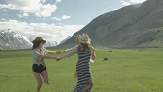 Trendy Hipster Girls having fun outdoor. Three cute women are whirling on green grass. Best friends.