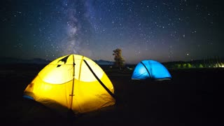 Two travelers watching the meteor shower in summer time. Timelapse of stars moving in night sky over the camp tent