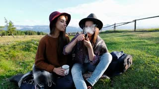 two young women smoking marijuana from a bowl in nature against a background of a mountain landscape 20s 4k.