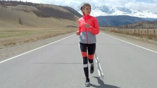Woman running alone at beautiful sunset on the road. Autumn sport and freedom concept. Athlete training on dusk. 20s 4k