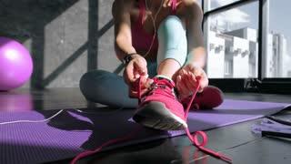 Woman tying shoelaces of sneaker on a floor 20s 4k.