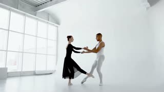 Young 20s ballet dancer gently holds the attractive brunette ballerina during the dance in white dance hall with big window slow motion 120fps.