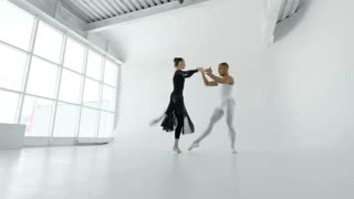 Young and attractive dancers in white and black gracefully dance in a white ballet hall with a large window shot from below 4k.