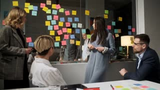 Young Business Team Brainstorming Ideas On Sticky Notes Attached To Glass Wall. Colleagues approve. Business Success Concept