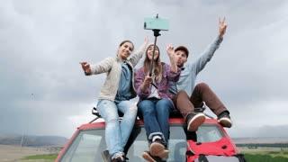 Young happy friends sitting on car outdoors make selfie by phone 20s 4k.