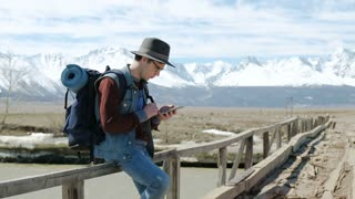 Young Man Traveler with backpack, Viewing map in digital mobile phone relaxing outdoor on background. 20s 4k