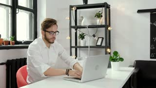 Young man working in office alone and smiling 20s 4k.