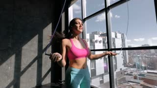Young pretty athletics girls skipping on drill at gym against barred window. 20s 4k.