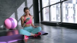 Young woman with smartphone at the gym,workout break 20s 4k