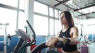 Woman 20s wearing smart watch working out on exercise bike 20s. 1080p Slow Motion