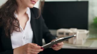 woman holding a tablet with app mobile wallet. house or home model