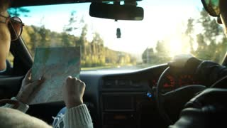 Woman holding map and showing the route map to her boyfriend driving the car.