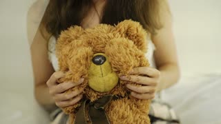 Woman holding teddy bear. Close up. White background 4k 20s