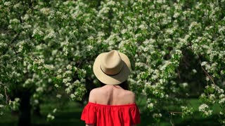 Woman in blooming trees.