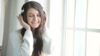 Woman listening music in headphones on windowsill background