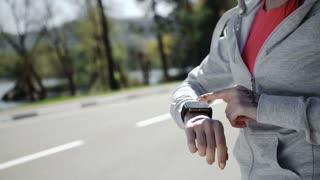 Woman setting up the fitness smart watch for running.