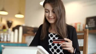 Woman shopping using tablet pc and credit card . indoor. close-up