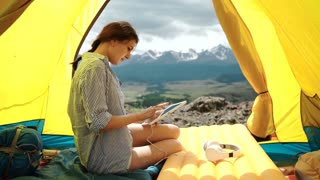 Woman smiling and using a tablet on a tent