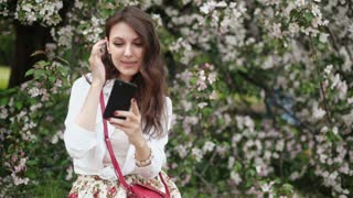 woman standing on the meadow at the blooming tree , using smartphone