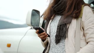 Woman using gps navigation on the smart phone near the car on the road